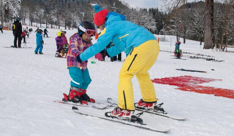 Skilehrerin kümmert sich um Kind