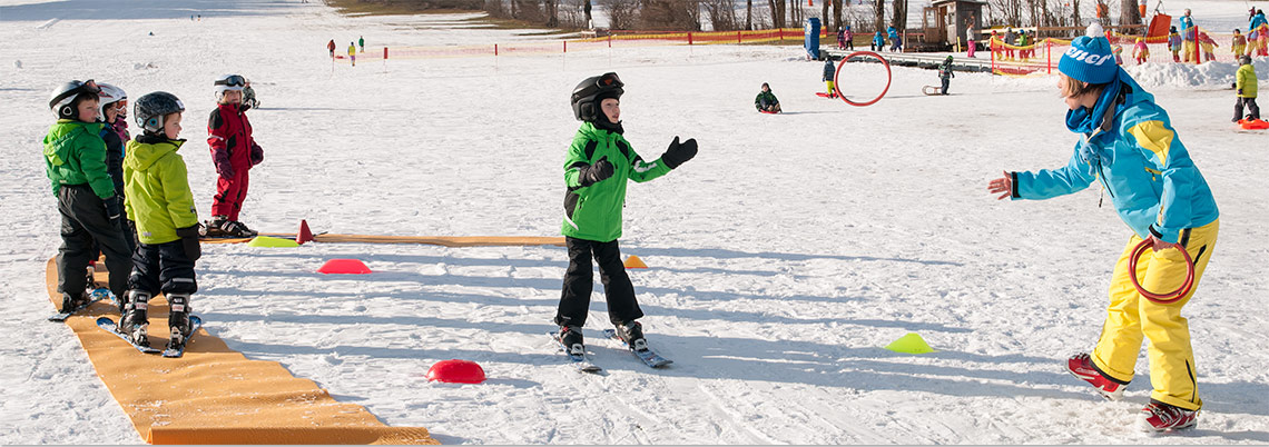 Skikurskinder schauen Kind beim Fangen eines Ringes zu