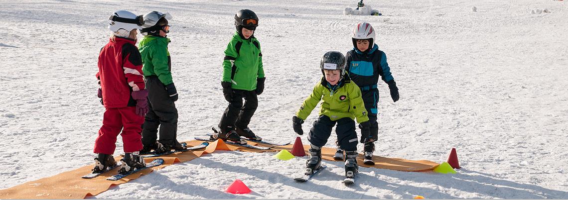 Kinder schauen sich zu wie sie zum ersten mal einen Berg hinunterfahren